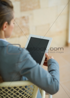 Business woman holding tablet PC. Rear view