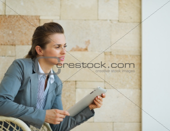Thoughtful business woman holding tablet PC and looking on copy space