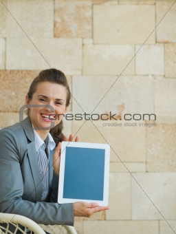 Smiling business woman showing tablet PC
