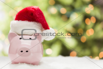 Pink Piggy Bank Wearing Red and White Santa Hat on Snowflakes with Abstract Green and Golden Background - Room for Your Own Text.