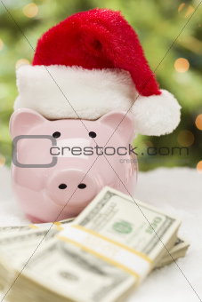 Pink Piggy Bank Wearing Santa Hat Near Stacks of Hundreds of Dollars of Money on Snowflakes.