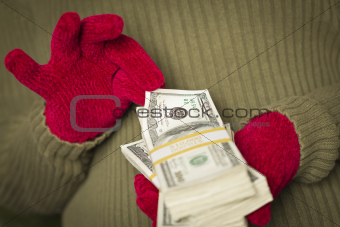 Woman Wearing Red Mittens and Green Sweater Holding Stacks of Hundreds of Dollars of Money with Red Ribbon.