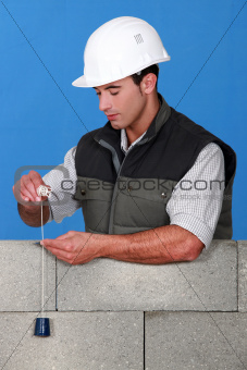 Mason checking quality of wall