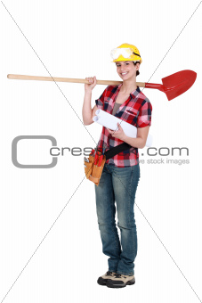 Female construction worker holding plans and spade