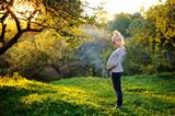 Beautiful pregnant woman stands next to the sunset