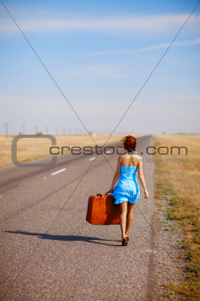 girl with luggage on the road