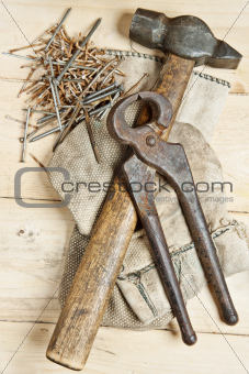 Vintage hammer and pliers with nails on wood background