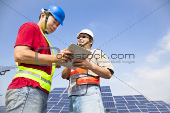 two workers  discussing with tablet pc before  solar power stat