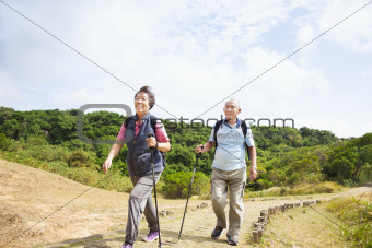 happy asian senior couple hiking