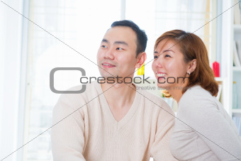 Asian couple looking away