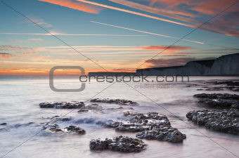 Beautiful sunset over Summer ocean with cliffs, rocks and vibran