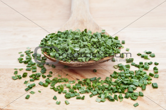 Chopped chives on wooden serving spoon with selective focus
