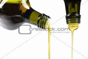 olive oil pouring from glass bottle isolated on white
