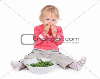 small girl eating grean peas