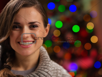 Portrait of happy young woman in front of Christmas lights