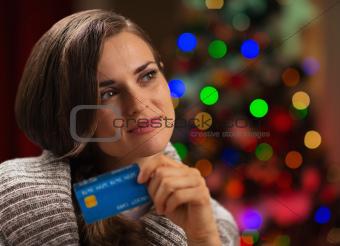 Portrait of thoughtful woman with credit card in front of Christmas lights
