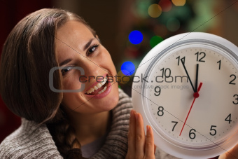 Portrait of smiling young woman showing clock in front of Christmas lights