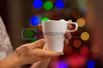 Closeup on cup with hot beverage in front of Christmas lights