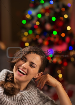 Portrait of smiling young woman in front of Christmas lights