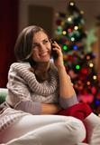 Young woman speaking mobile phone in front of Christmas tree