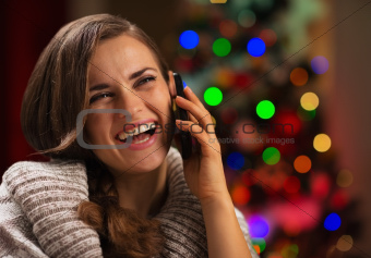 Smiling young woman speaking mobile phone in front of Christmas lights