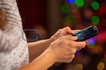 Closeup on mobile phone in hand of happy girl in front of Christmas lights