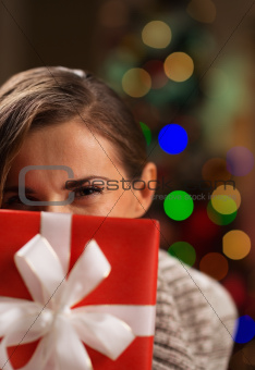 Girl hiding behind Christmas present box