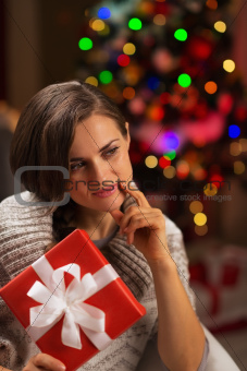 Thoughtful young woman with Christmas present box