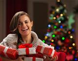 Happy young woman holding Christmas present boxes