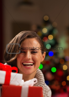 Happy young woman looking out from Christmas gift boxes