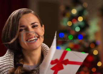 Happy young woman with Christmas postcard
