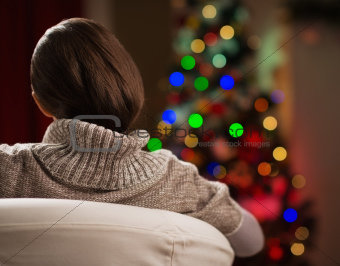 Young woman looking on Christmas tree. Rear view