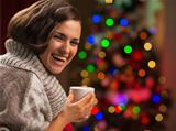 Happy young woman with cup of hot chocolate in front of Christmas tree