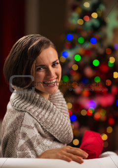 Happy young woman sitting in front of Christmas tree