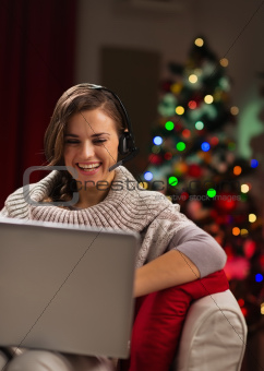 Happy young woman having video chat with family in front of Christmas tree