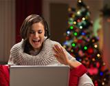 Happy young woman having Christmas video chat with family