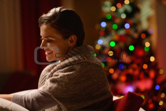 Happy young woman sitting chair in front of Christmas tree