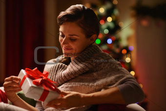 Happy young woman sitting chair with Christmas present box
