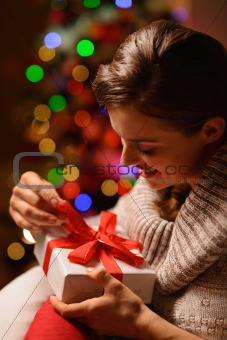 Happy young woman sitting chair and opening Christmas present box