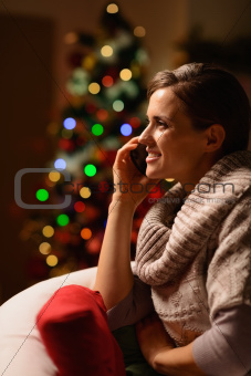Young woman sitting chair and making phone call in front of Christmas tree