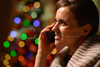 Young woman sitting chair and making phone call in front of Christmas lights