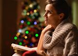 Dreaming young woman sitting chair and reading book in front of Christmas tree