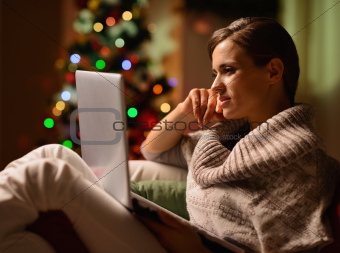 Young woman sitting chair with laptop in front of Christmas tree