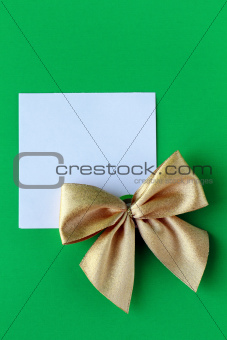 white blank with a gold bow on a green background