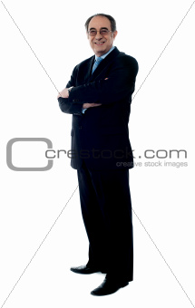Smiling senior executive posing with folded arms