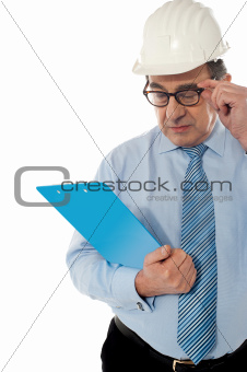 Experienced achitect in hardhat studying files. Isolated on white