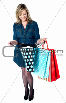 Fashionable woman looking into shopping bags