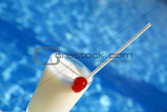 cocktail in glass with a cherry on a background blue water of pool