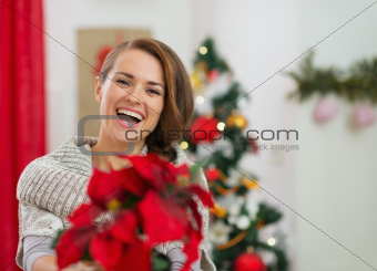 Smiling young woman holding Christmas rose near Christmas tree