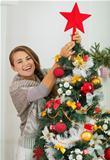 Happy young woman hanging Christmas top on Christmas tree